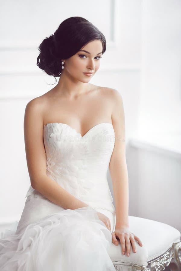 Bruid in mooie kledingszitting op stoel binnen royalty-vrije stock foto's