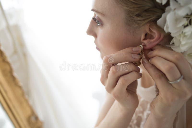 Bruid om de oorringen te zetten royalty-vrije stock fotografie