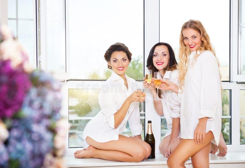 Bruid om te zijn en bruids vrienden die glas met champagne houden stock fotografie