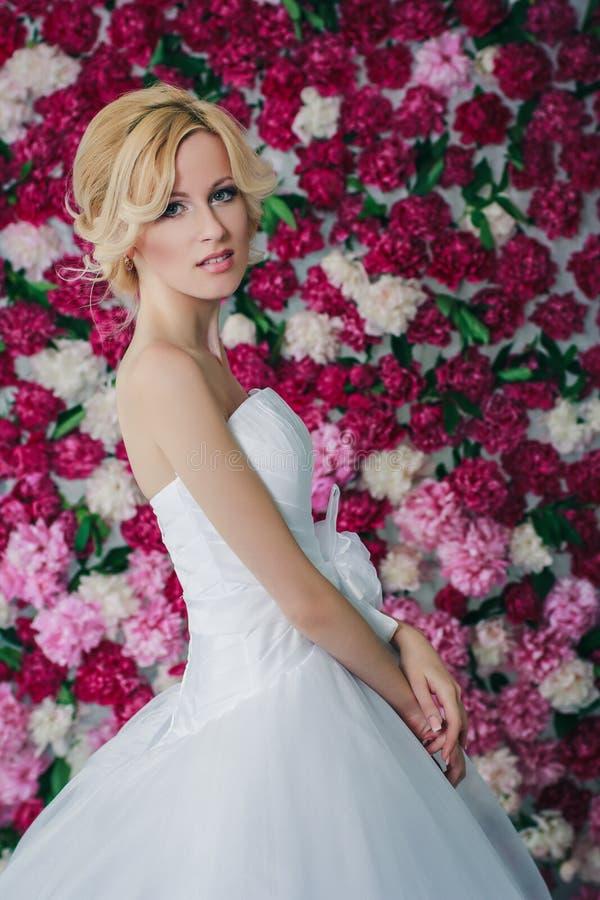 Bruid op de pioenachtergrond stock foto's