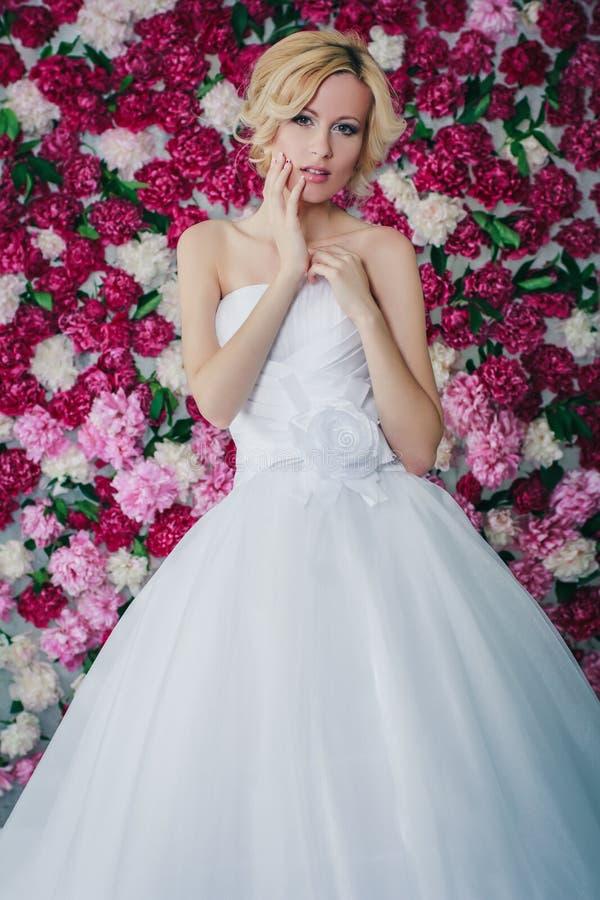 Bruid op de pioenachtergrond stock afbeelding
