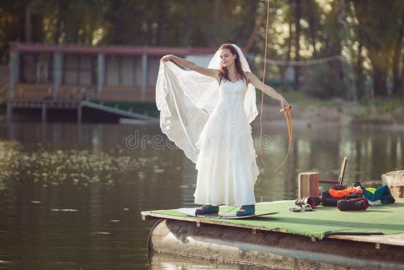 Bruid op een wakeboard op het meer royalty-vrije stock afbeeldingen