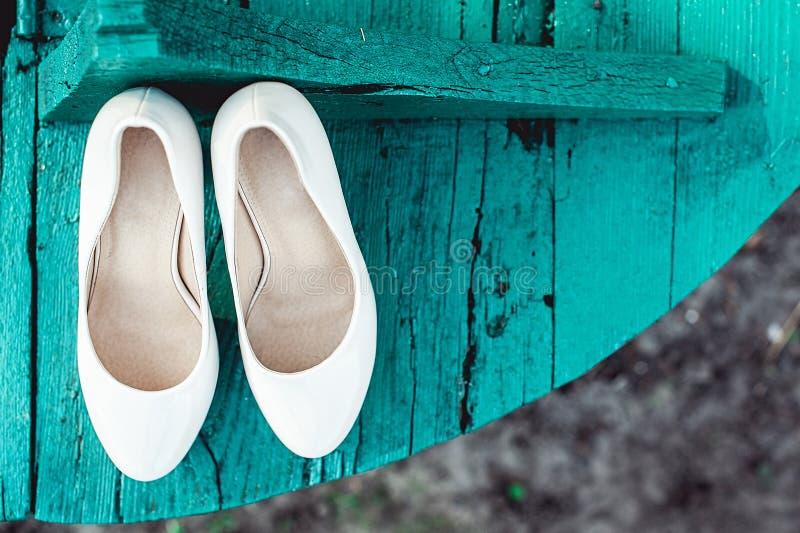 Bruid` s biege schoenen op hiel op een houten raads tiffany kleur stock foto