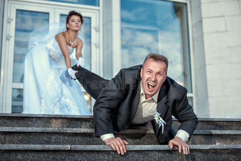 Bruid slepende bruidegom bij het huwelijk royalty-vrije stock fotografie