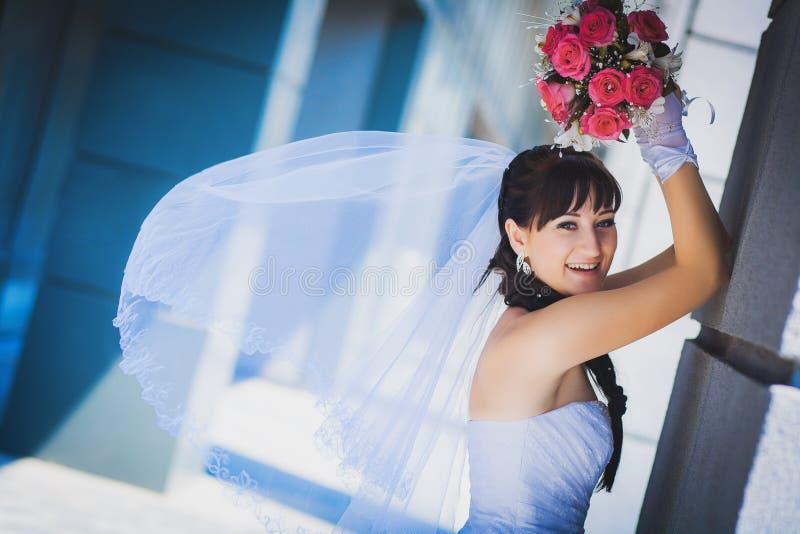 Bruid tegen een blauwe moderne de bouwachtergrond royalty-vrije stock fotografie