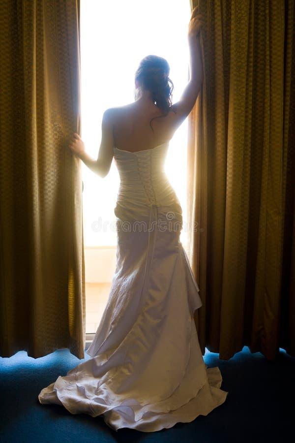 Bruid van achter het kijken door gordijnen stock foto