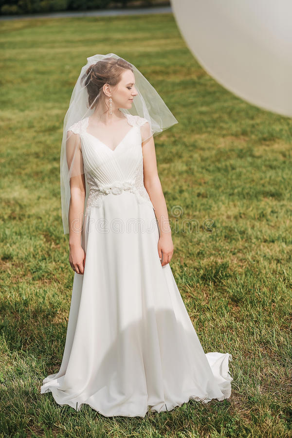 Bruid in witte kleding die zich op groene weide bevinden stock afbeelding