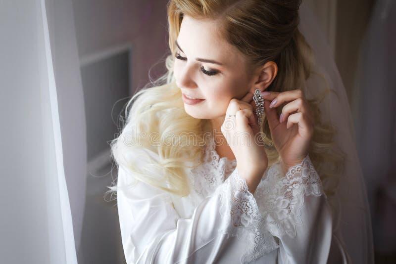 Bruid in witte peignoir die oorringen dragen royalty-vrije stock afbeelding