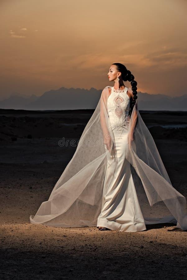Bruid in zandduinen op berglandschap royalty-vrije stock foto's