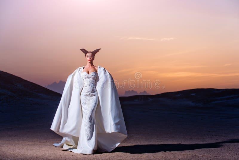 Bruid in zandduinen op berglandschap royalty-vrije stock afbeelding