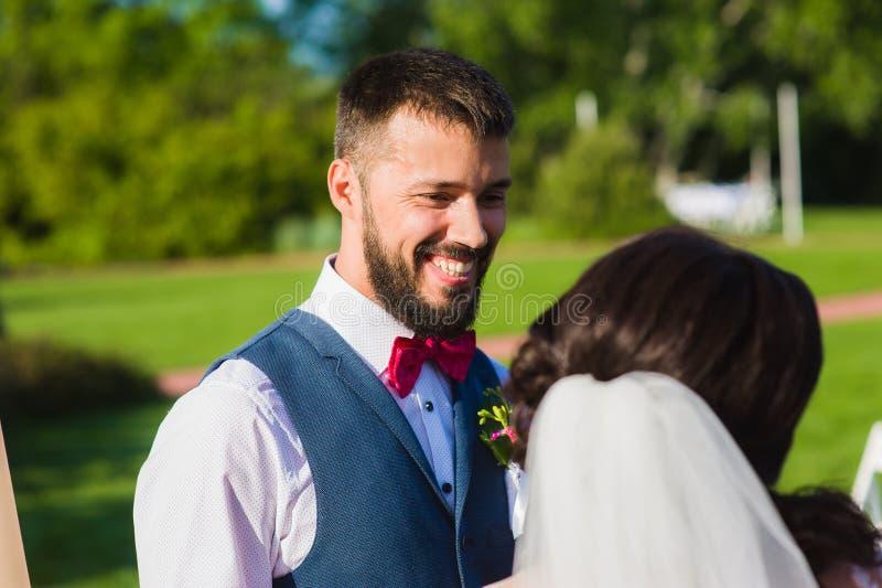 Bruidegom die aan zijn bruid met een sluier glimlachen royalty-vrije stock fotografie