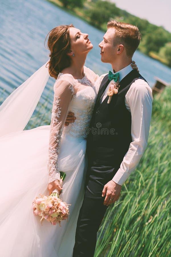 Bruidegom die bruid omhelzen dichtbij blauwe vijver royalty-vrije stock foto's