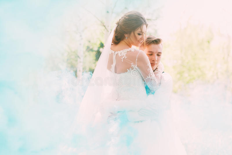 Bruidegom die bruid in turkooise rook op aard omhelzen stock foto's