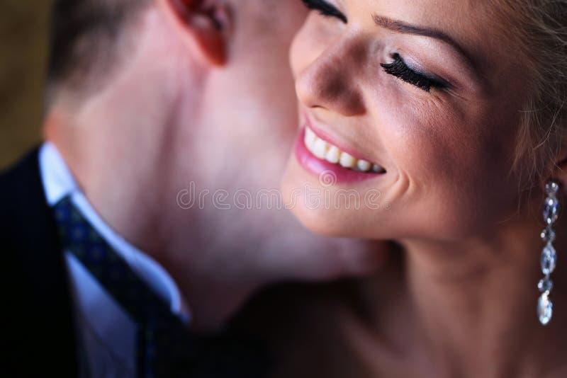 Bruidegom die de bruid in een zacht licht kussen stock afbeeldingen