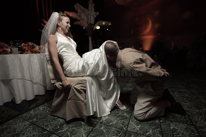 Bruidegom die de kouseband verwijdert royalty-vrije stock foto's