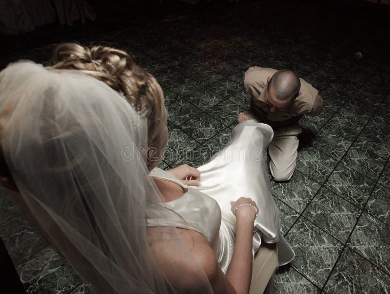 Bruidegom die de kouseband verwijdert stock foto