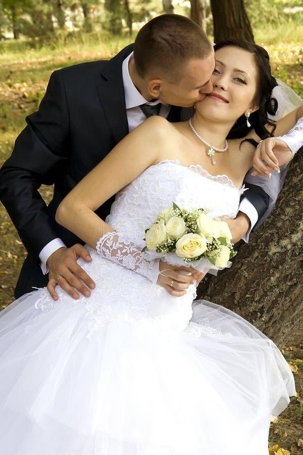 Bruidegom die een bruid kust stock foto