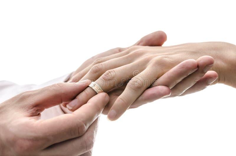 Bruidegom die een trouwring op de vinger van de bruid zetten stock afbeelding