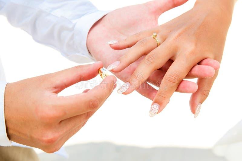 Bruidegom die een verlovingsring geven aan zijn bruid onder boogdeco royalty-vrije stock foto