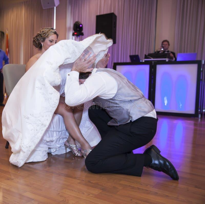 Bruidegom die kouseband opstijgen royalty-vrije stock foto's