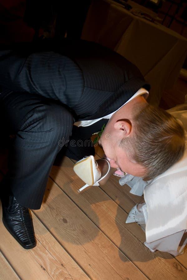 Bruidegom die kouseband verwijdert royalty-vrije stock fotografie