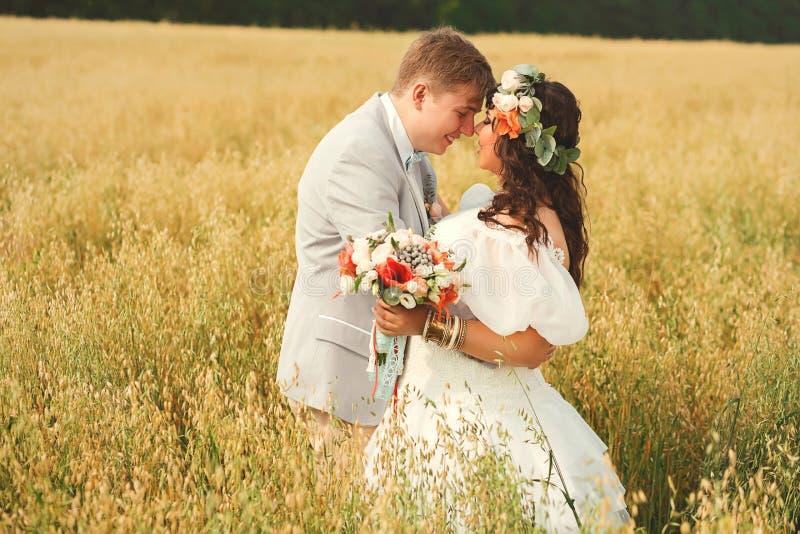 Bruidegom die met bruid op geel gebied omhelzen royalty-vrije stock foto's