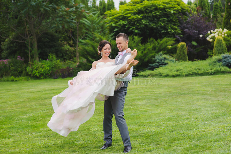 Bruidegom die mooie bruid in zijn wapens houden royalty-vrije stock fotografie