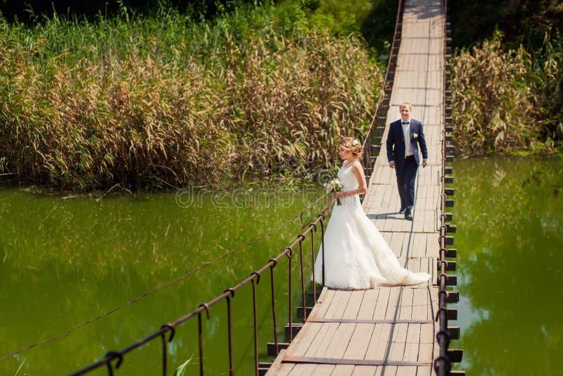 Bruidegom die naar bruid langs de brug gaan stock foto's