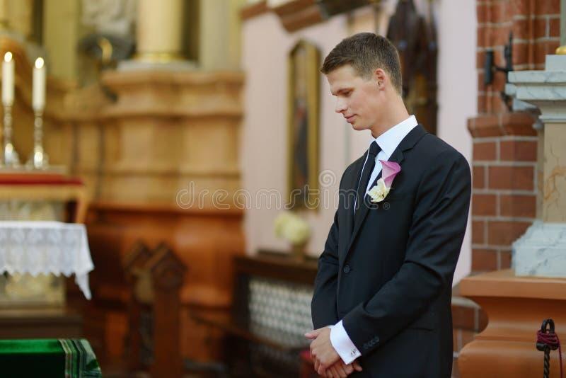 Bruidegom die op de bruid in kerk wachten stock afbeelding