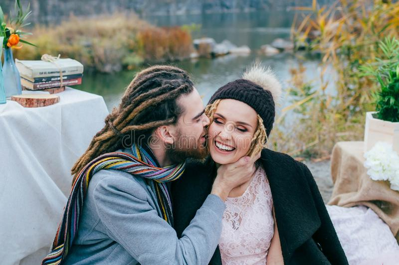 Bruidegom die teder haar mooie bruid in wang kussen De ceremonie van het de herfsthuwelijk in rustieke stijl in openlucht De jong royalty-vrije stock fotografie