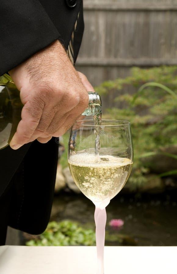 Bruidegom die Witte Wijn giet royalty-vrije stock foto's