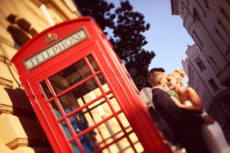 Bruidegom en bruid dichtbij phonebooth stock fotografie