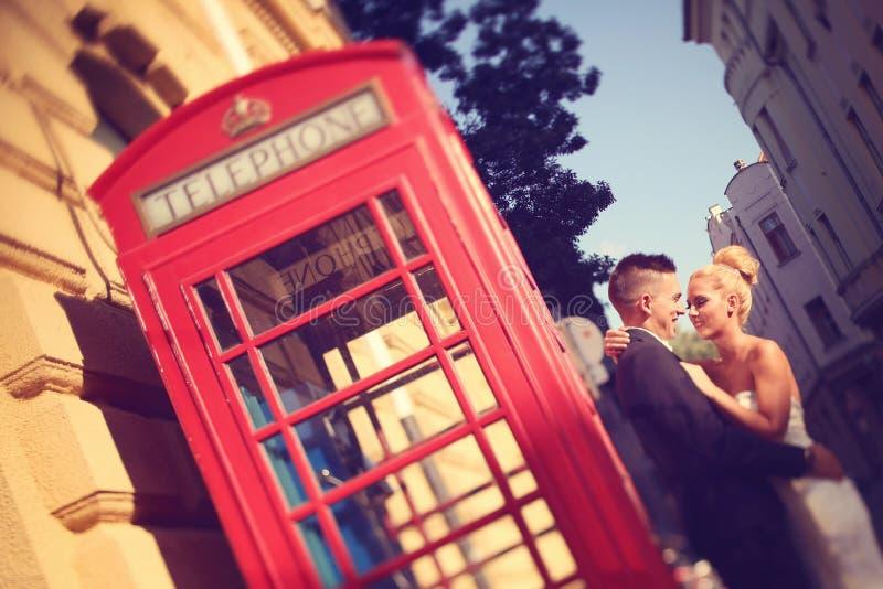 Bruidegom en bruid dichtbij phonebooth stock afbeelding