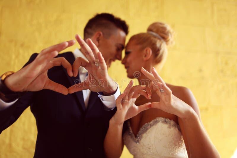 Bruidegom en bruid die liefdeteken met hun handen maken stock fotografie