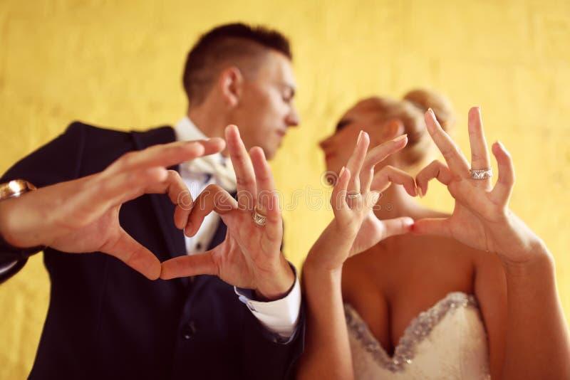 Bruidegom en bruid die liefdeteken met hun handen maken royalty-vrije stock afbeelding