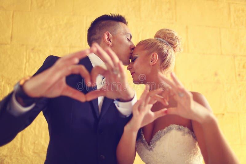 Bruidegom en bruid die liefdeteken met hun handen maken stock afbeeldingen