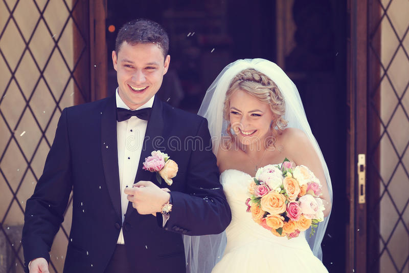 Bruidegom en bruid die van kerk weggaan stock afbeeldingen