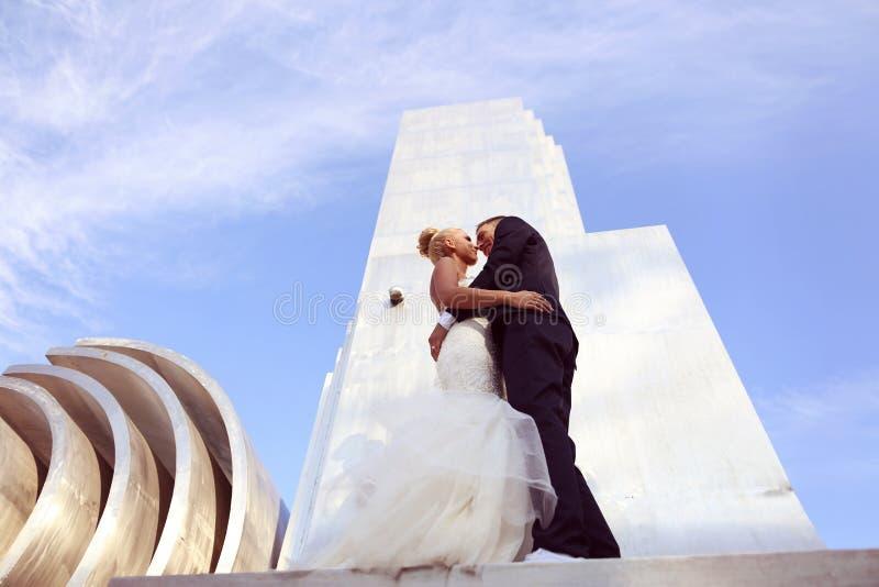 Bruidegom en bruid het kussen op een grote metaalbouw royalty-vrije stock foto