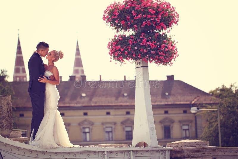 Bruidegom en bruid het kussen op een metaalbrug stock afbeelding