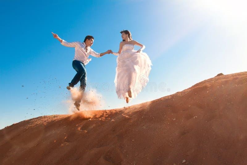 Bruidegom en bruid het springen stock foto's