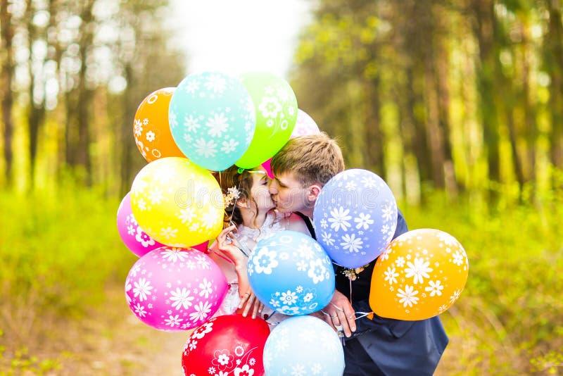 Bruidegom en bruid met ballons openlucht stock foto's