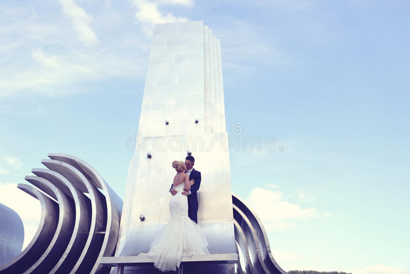 Bruidegom en bruid op een grote metaalbouw royalty-vrije stock afbeeldingen