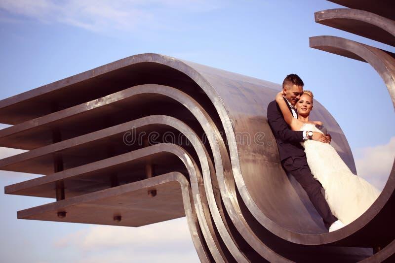 Bruidegom en bruid op een grote metaalbouw royalty-vrije stock afbeelding