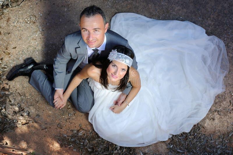 Bruidegom en bruidholdingshanden die op de vloer zitten royalty-vrije stock foto