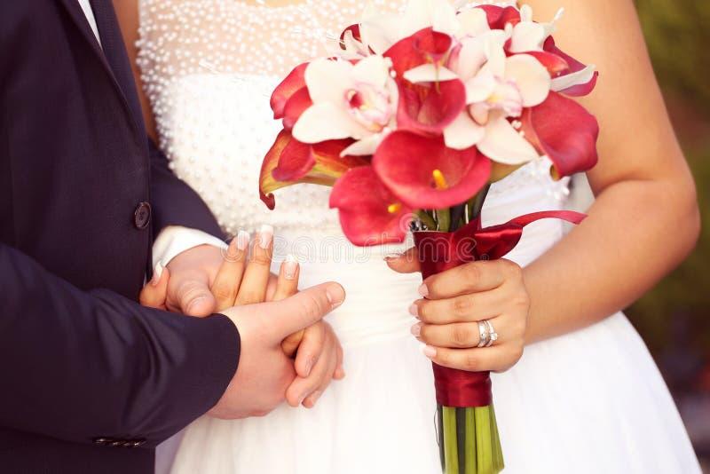 Bruidegom en bruidholdingshanden en huwelijksboeket stock foto's