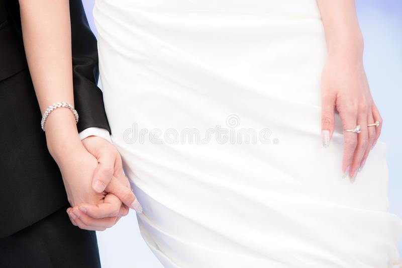 Bruidegom en Bruidholdingshanden met ringen op hun vingers stock foto