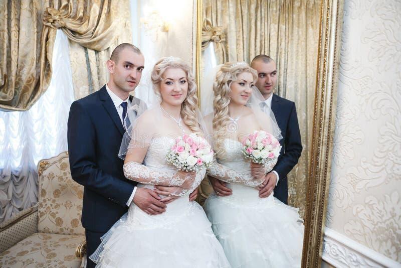 Bruidegom en de bruidtribune dichtbij een spiegel royalty-vrije stock foto