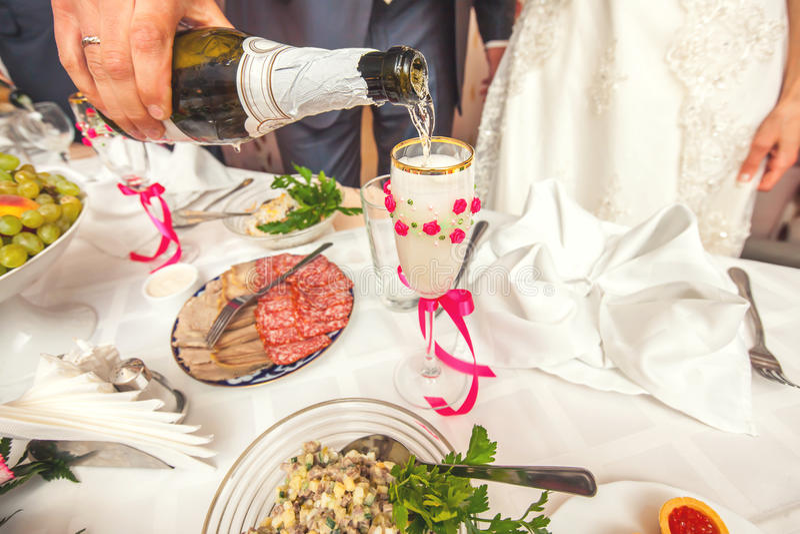 Bruidegom gietende champagne stock afbeelding