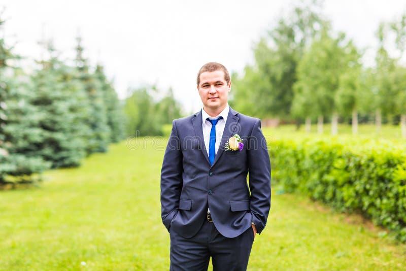 Bruidegom in kostuum op de aard Mannelijk portret in openlucht Knappe kerel in openlucht royalty-vrije stock foto's