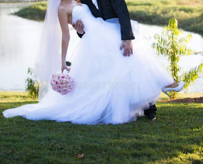 Bruidegom Leans Into Bride voor Kus stock fotografie